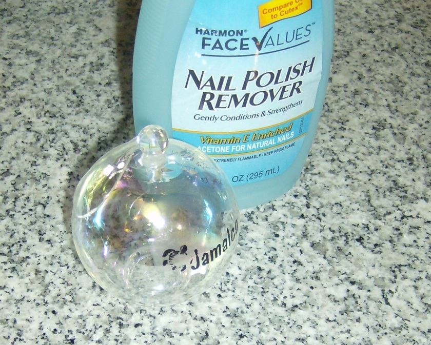 Using finger nail polish remover to erase the word printed on the ornament. Photo by Holly Tierney-Bedord. All rights reserved.