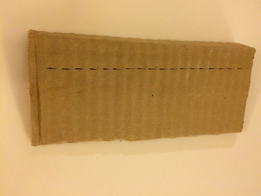 Score your cardboard with an exacto knife or scissor edge and it will easily fold like you need it to. The score should be on the outside, not the inside.